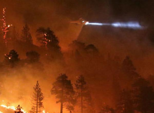 Los Angeles county fire helicopter makes a water drop to battle wild land fire call the Pine Fire in Wrightwood, Calif., on July 17. A late night brush fire broke out near the Mountain High ski resort Friday in the hills of the Angeles Forest.